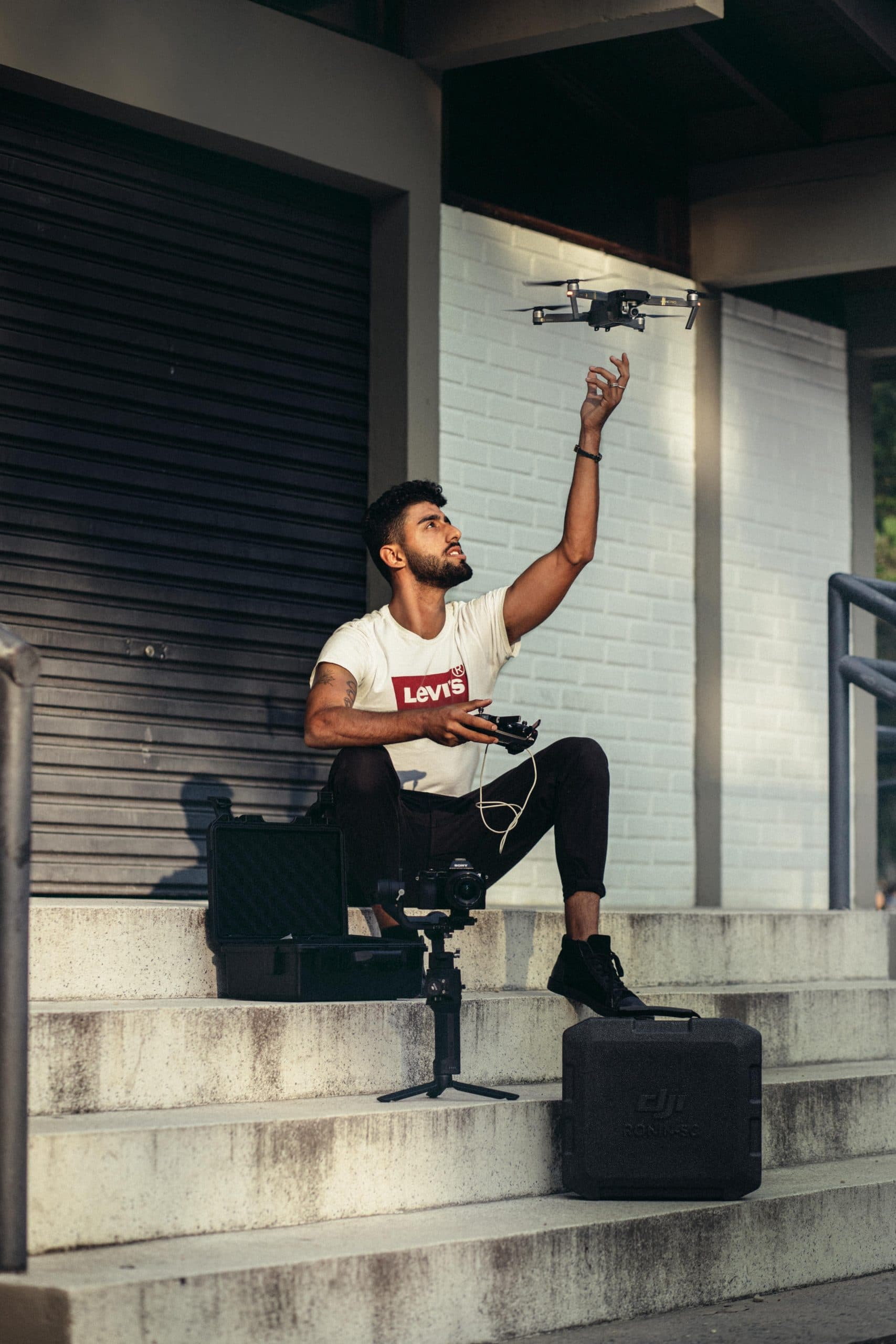 man-in-white-shirt-holding-remote-of-a-drone-3230313