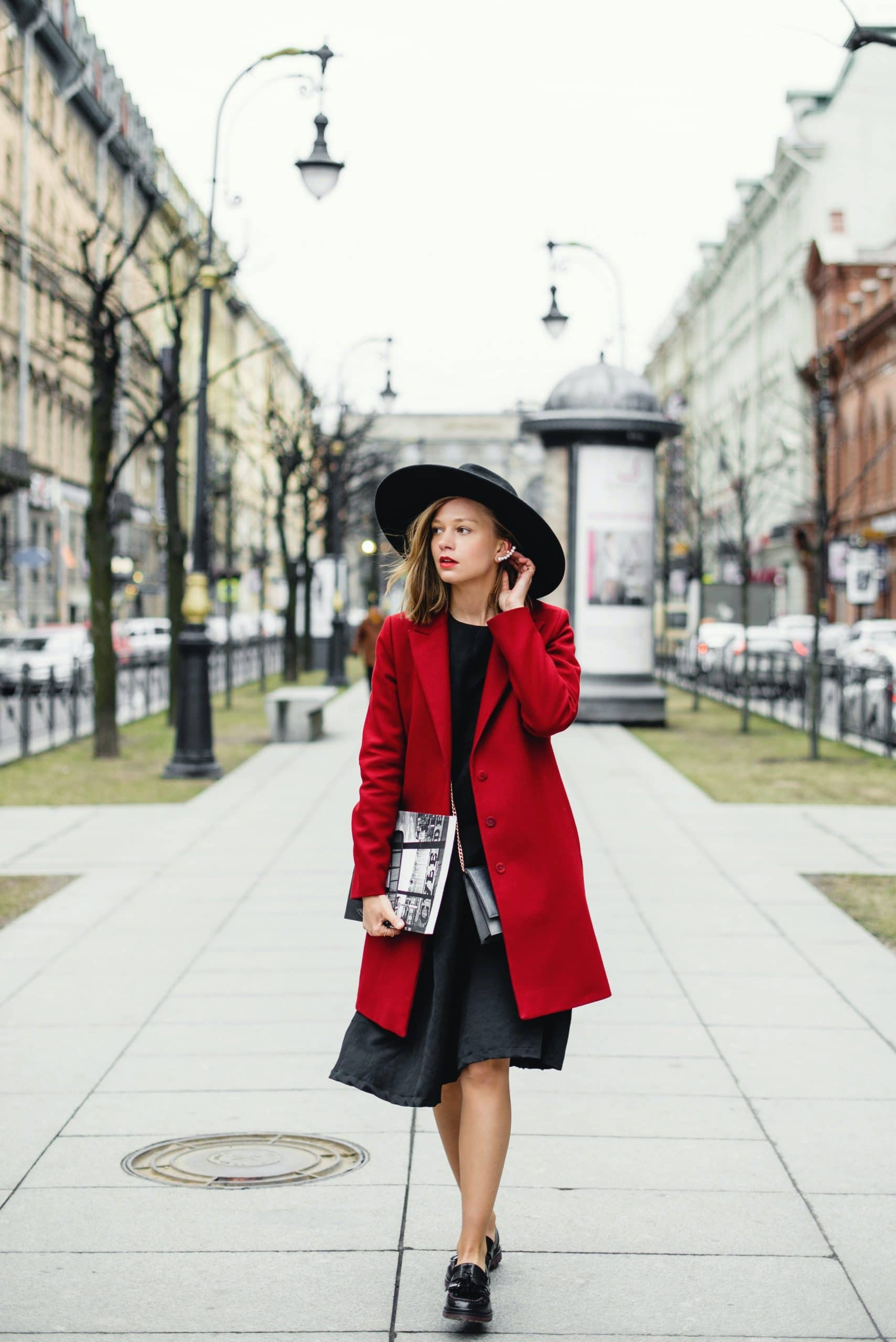 woman-in-red-coat-and-black-skirt-walking-on-sidewalk-3951783