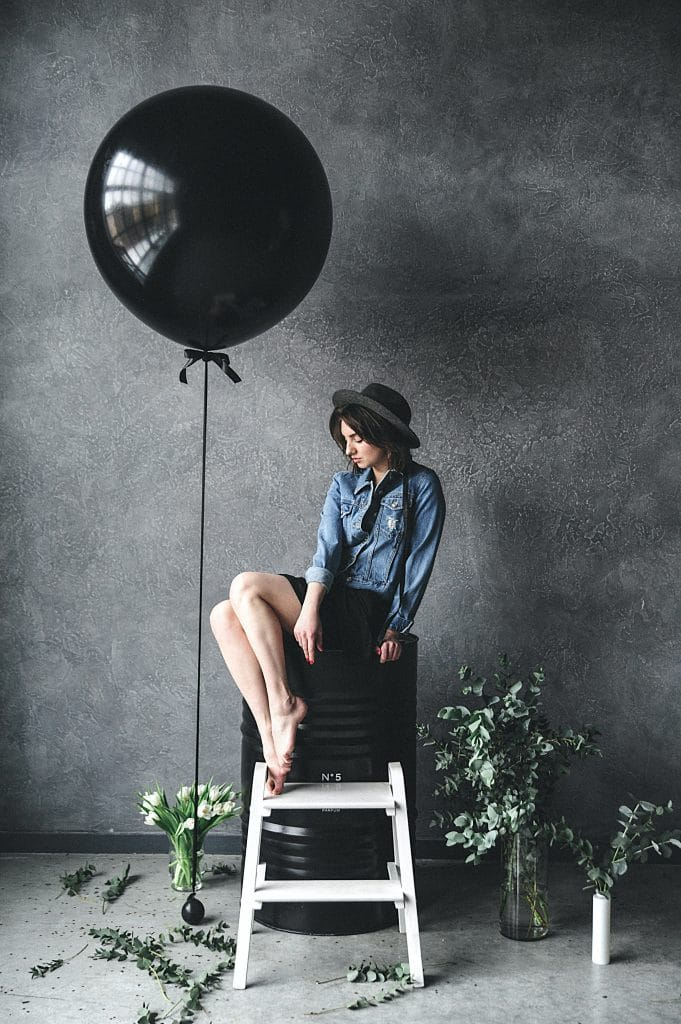 woman-sitting-on-chair-beside-balloon-1391580