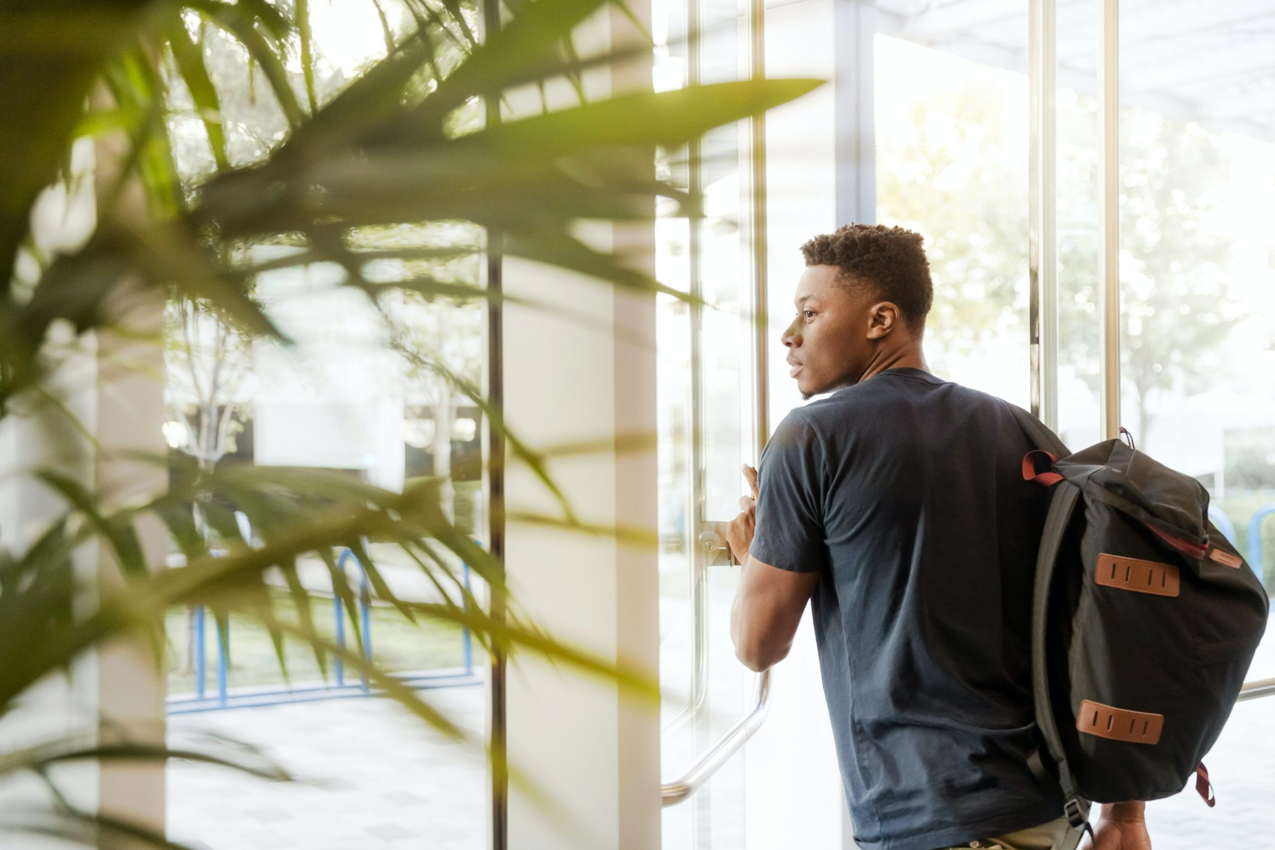man-looking-outside-window-carrying-black-and-brown-backpack-1251861