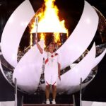 Naomi Osaka holds the Olympic torch in Tokyo.